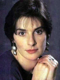 Enya: full face, wearing silver earrings and dark dress