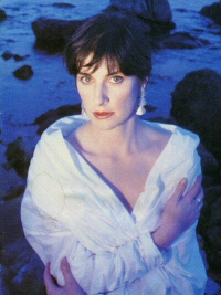 Orinoco Flow press shot: Enya on beach in white wrap dress with water and rocks behind her.